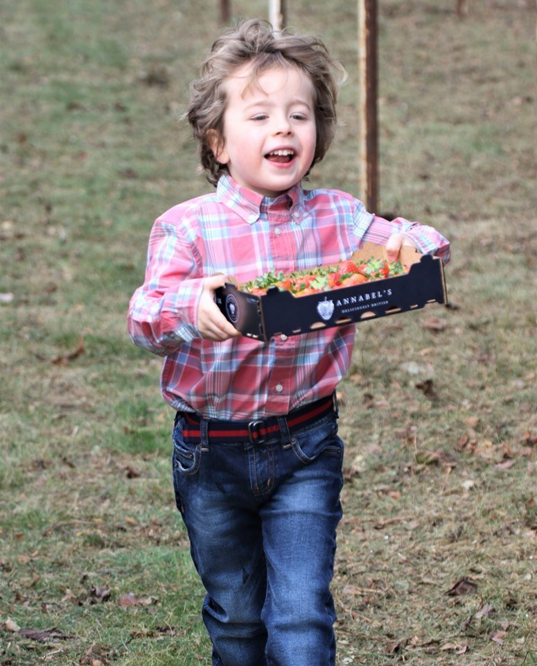 Oscar Makin-Jones running with a box of strawberries