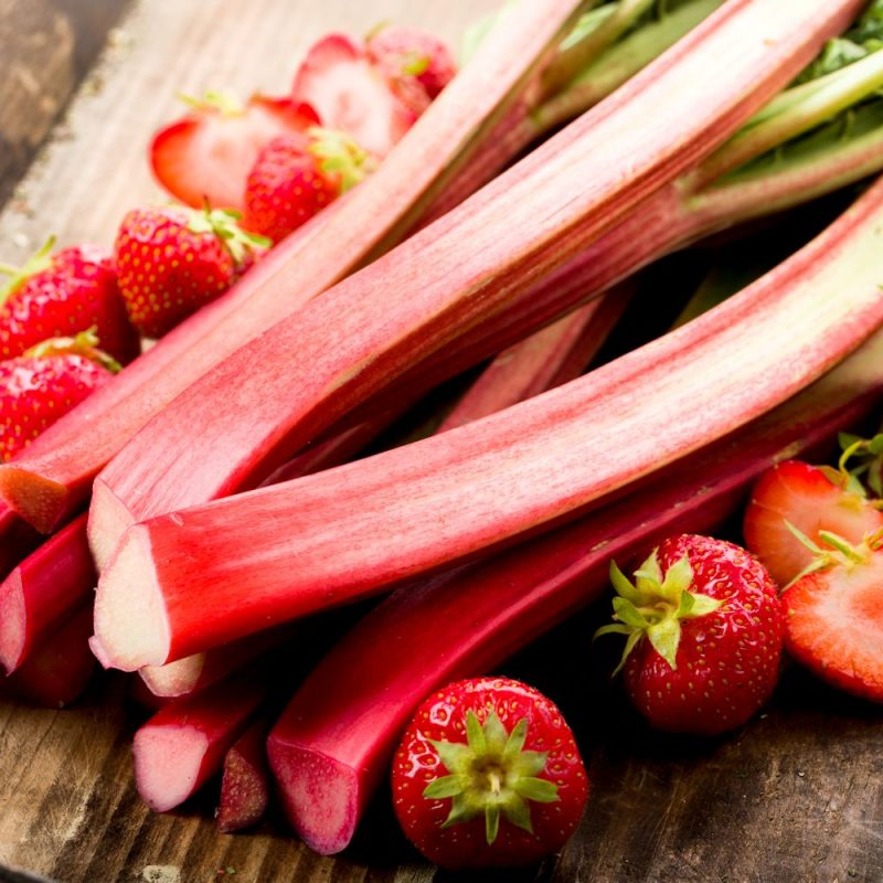 Rhubarb and strawberry's on a wooden plate