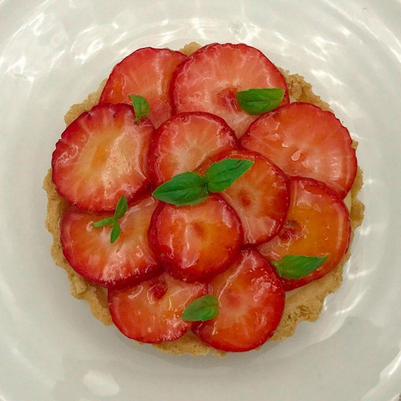 Strawberry, elderflower and basil tart sitting on a white plate