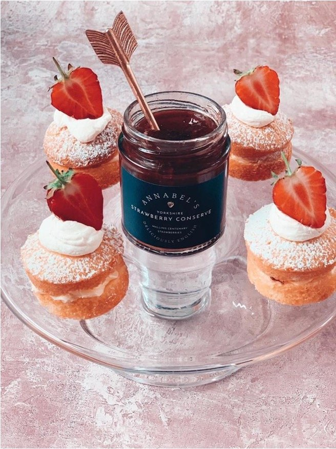 Strawberry topped mini sponge cakes surrounding a jar of Annabel's Strawberry Conserve