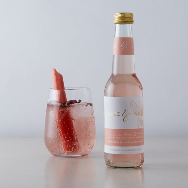 A bottle and glass of Tame and Wild rhubarb, elderberry rose