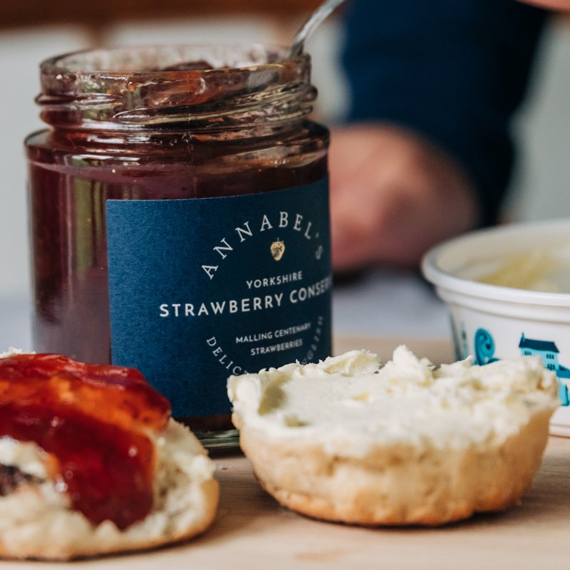 Close up of a jar of strawberry conserve with scones